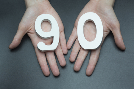 Female hand with number ninety.