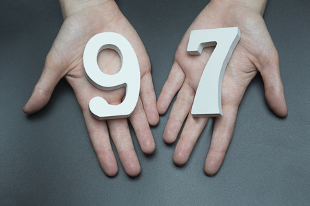 Female hand with numbers ninety-seven. Imagens