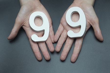 Female hand with numbers ninety-nine.
