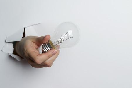 Female hand holding bulb Isolated on white background.