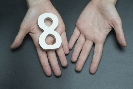 Female hand with a number eight.