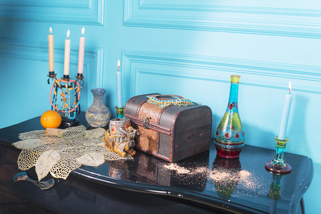 A chest, candles and a bottle stand on the table.