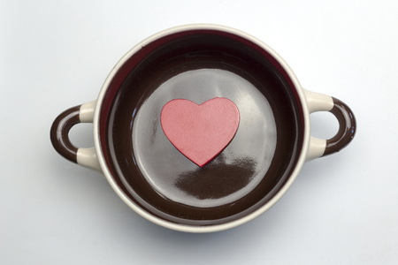 Big red heart at the bottom of the soup tureen on white background.