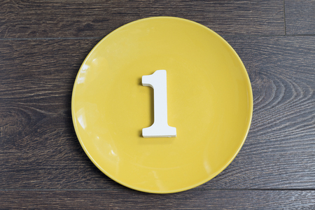 Number 1 on a yellow plate against wooden background