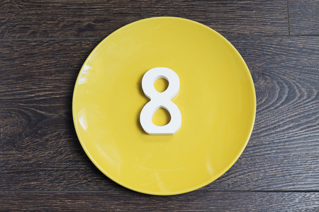 Number 8 on a yellow plate against wooden background