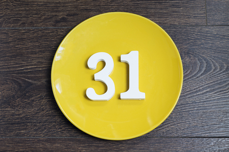 Number 31 on a yellow plate against wooden background Banco de Imagens