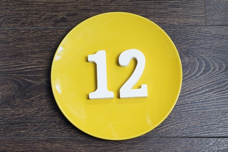 Number 12 on a yellow plate against wooden background