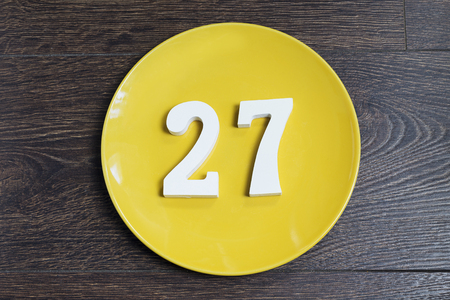 Number 27 on a yellow plate against wooden background Imagens