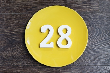 Number 28 on a yellow plate against wooden background