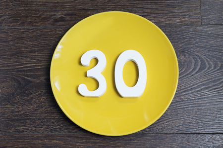 Number 30 on a yellow plate against wooden background