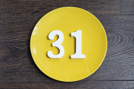 Number 31 on a yellow plate against wooden background Imagens