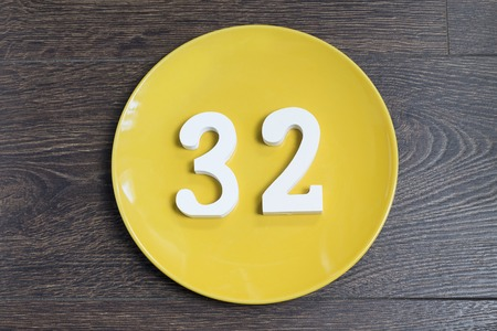 Number 32 on a yellow plate against wooden background Imagens