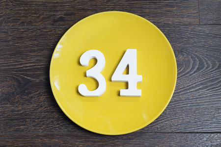 Number 34 on a yellow plate against wooden background