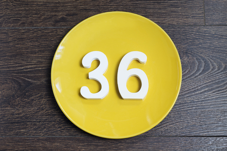 Number 36 on a yellow plate against wooden background