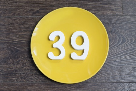 Number 39 on a yellow plate against wooden background