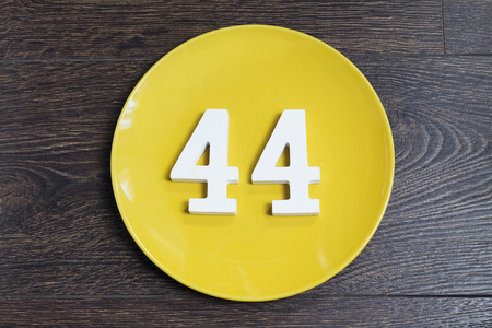 Number 44 on a yellow plate against wooden background
