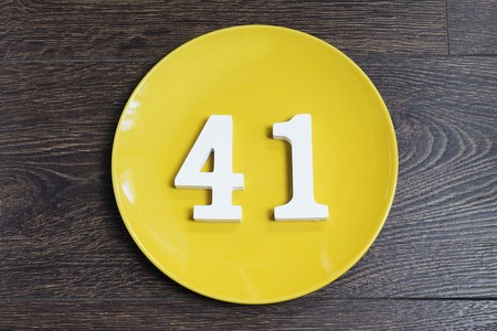 Number 41 on a yellow plate against wooden background