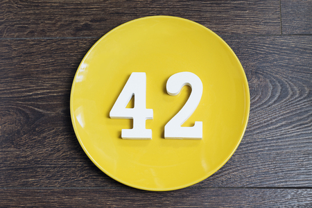 Number 42 on a yellow plate against wooden background