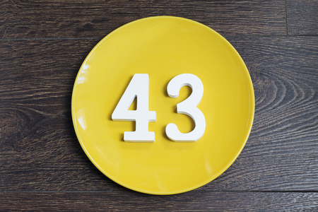 Number 43 on a yellow plate against wooden background
