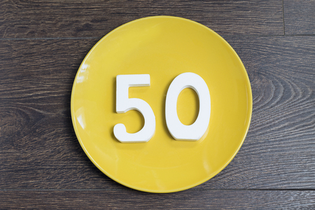 Number 50 on a yellow plate against wooden background