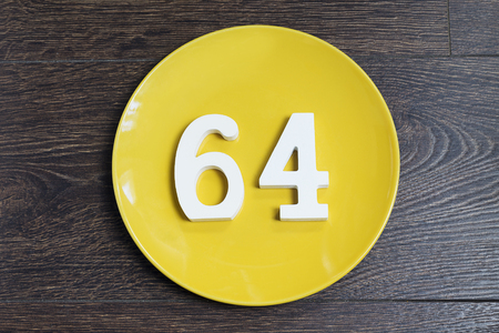 Number 64 on a yellow plate and wooden background.