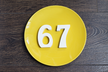 Number 67 on a yellow plate and wooden background.