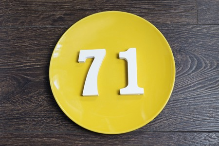 Number 71 on a yellow plate and wooden background.