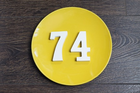Number 74 on a yellow plate and wooden background.