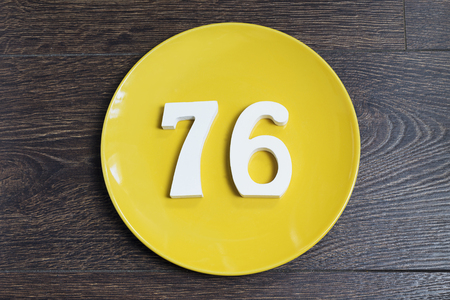 Number 5476on a yellow plate and wooden background.