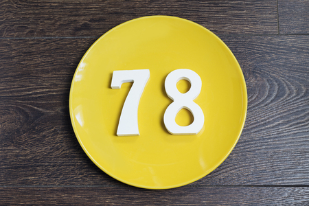 Number 78 on a yellow plate and wooden background. Banco de Imagens