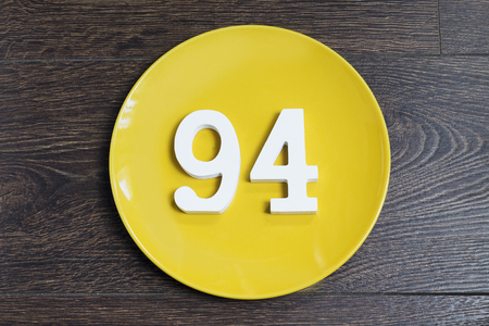 Numeral ninety-four on the yellow plate and brown background. Imagens