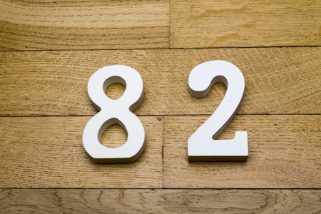 Figures eighty-two on a wooden, parquet floor as a background.