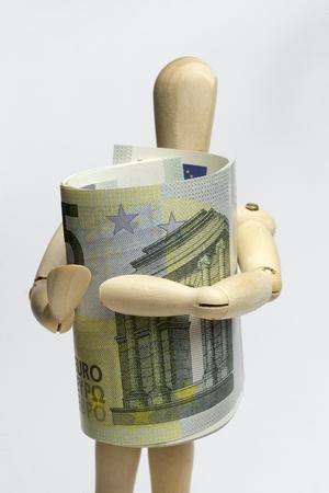 Wooden man holding five euros. Stock Photo