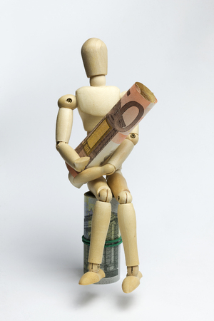 Wooden man holding fifty Euro.