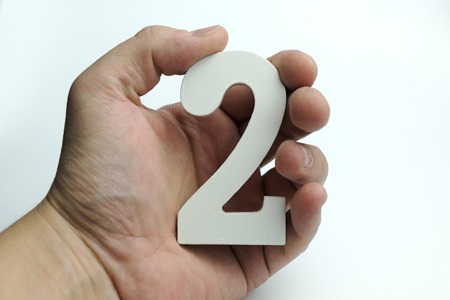 Hand holds the number two on white background.