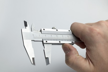 Hand holding caliper on a white background.