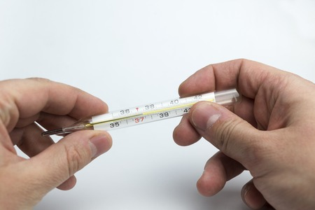 Hand holds a thermometer on a white background.