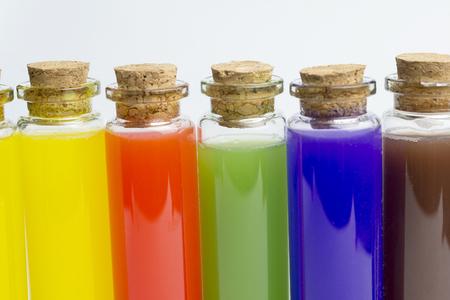 Líquidos de colores en cinco tubos de ensayo aislado sobre fondo blanco.