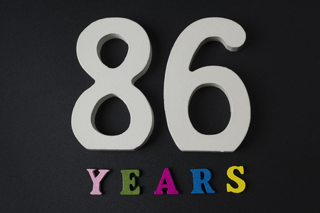 Letters and numbers eighty-six years on a black isolated background. Stock Photo