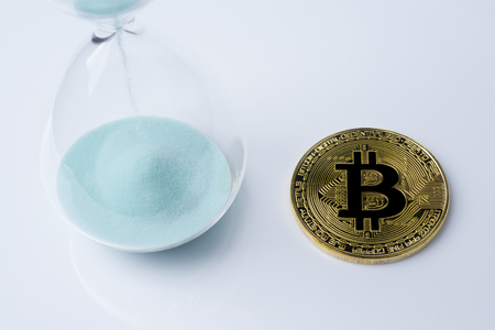 Gold bitcoin and hourglass on a white background. Imagens - 114137599