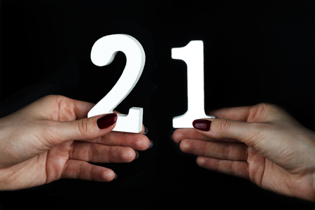 On a black background, female hand with number twenty-one. Imagens
