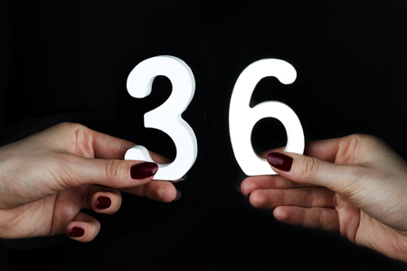 On a black background, female hand with number thirty-six.