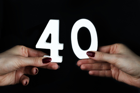 On a black background, female hand with the number forty.