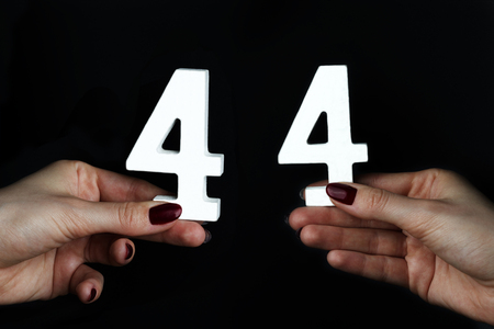 On a black background, female hand with number forty-four.