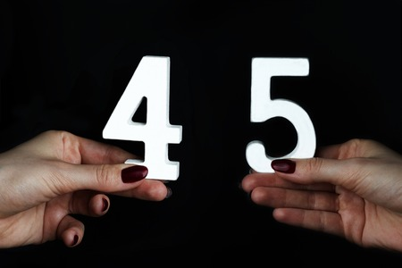 On a black background, female hand with number forty-five. Banco de Imagens