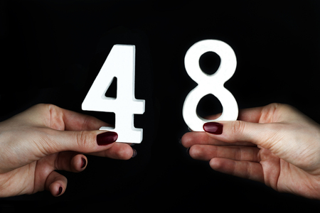 On a black background, female hand with number forty-eight. Imagens - 114134071