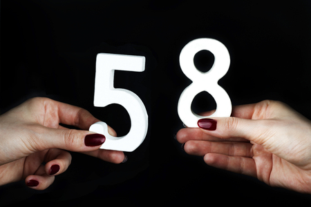 On a black background, female hand with the number sixty-five.