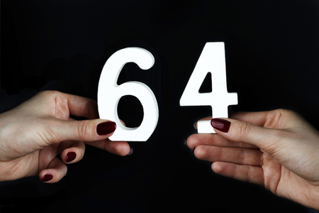 On a black background, female hand with number sixty-four.