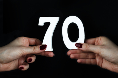 On a black background, female hand with the number seventy.