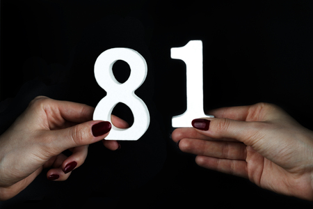 On a black background, female hand with numbers eighty-one.